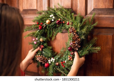 Back view of a young girl, hanging a christmas wreath on the door of her home. Preparation for winter holidays, house decoration, symbol.