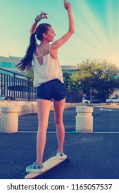 Back view of young girl in short overalls with long bare legs and long hair in ponytail riding skateboard with her hands rised, skater girl trying to keep balance