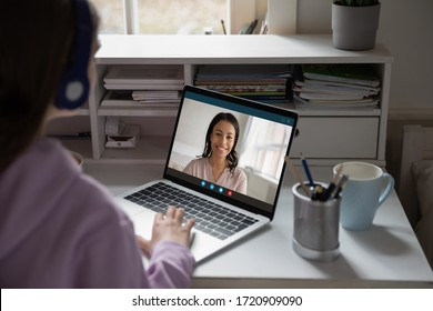 Back view of young girl sit at desk at home talk have online video call lesson with teacher or tutor, teenage schoolgirl engaged in webcam conversation, study distant use web conference app on laptop