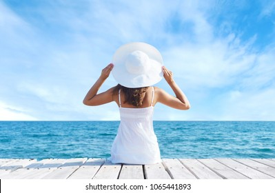 Back view of a young girl standing on a pier. Sea and sky background. Vacation and traveling concept.