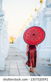 Back view of young girl with traditional burmese umbrella at beautiful white Kuthodaw Pagoda in Mandalay Myanmar