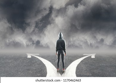 Back view of young hacker with two arrows on concrete road. Cloudy sky background. Different direction and malware concept