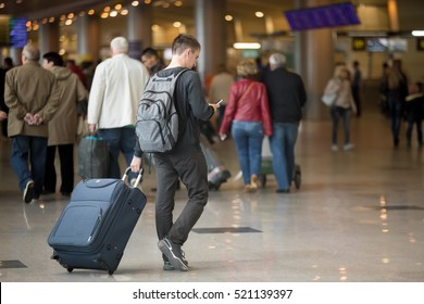 Back view of young handsome traveler walking in modern airport terminal, using smartphone app in public wifi area, messaging, travelling with luggage bag, wearing casual style clothes, copy space