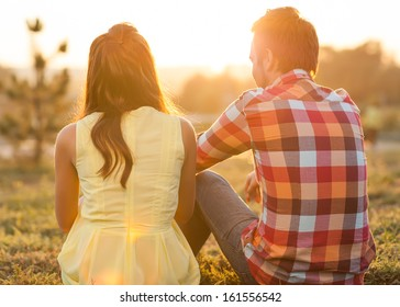 back view of young happy couple sitting on river at sunset