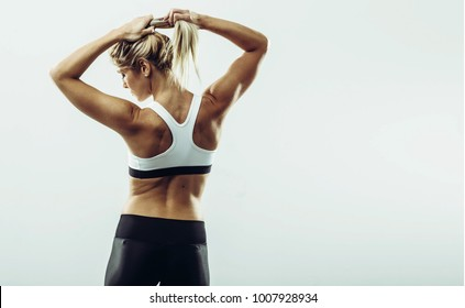 Back view of young healthy athlete woman. Young healthy athlete female posing at studio