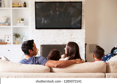 Back view of young Hispanic family of four sitting on the sofa watching TV, mum looking at dad