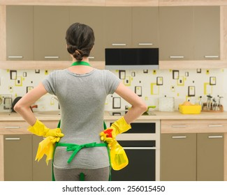 back view of young housewife getting ready for kitchen cleaning