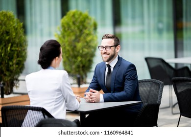 Back view of young lady in business dress and handsome successful male talking at cafe table