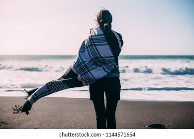 Back view of young lonely woman enjoying ocean. Depression