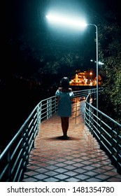 Back view of young lonely woman walking on the bridge at night