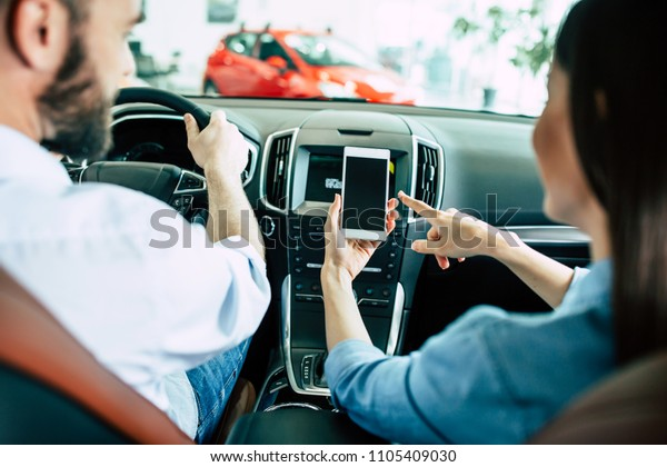 Back view of young Lover couple in car, man driving in city and woman using navigation on mobile phone or some apps