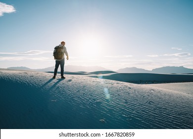 Back view of young male traveler exploring white sand desert on active vacation recreation, man explorer looking at beautiful scenery of sunset enjoying discover destination of wild environment