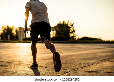 back view of young man athlete in casual silhouette running in the urban city on sunset