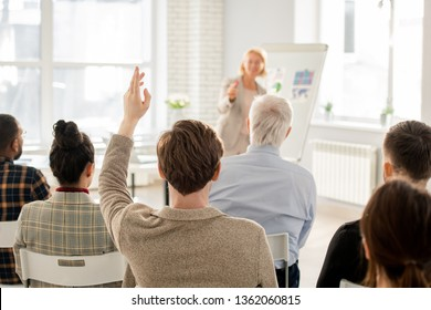 Back view of young man in casualwear raising his hand to answer question of teacher during lecture