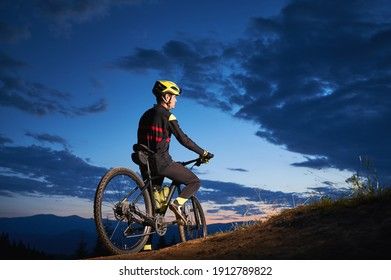 Back view of young man in cycling suit sitting on bicycle under blue night sky with clouds. Male bicyclist in safety helmet riding bicycle on the road in the evening. Concept of active leisure.
