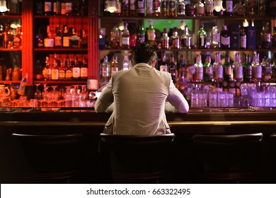 Back view of a young man drinking beer while while sitting at the bar counter
