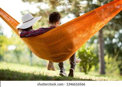 Back view of young man and girl in hammock in green forest