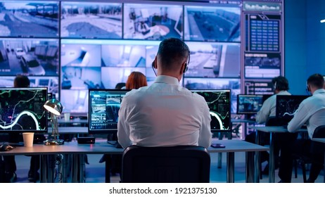 Back view of young man with headset watching surveillance footage and map on computers and speaking with female colleague while working in intelligence agency