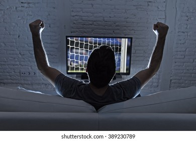 back view of young man home alone watching soccer or football game in television enjoying and celebrating goal and victory gesturing with fist sitting on the sofa happy and excited
