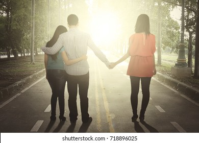 Back view of young man hugging his wife while holding a hand of another woman. Shot at outdoor