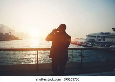 Back view of a young man intelligent financier is drinking take away coffee, while is resting after work day. Silhouette of a male manager is standing outdoors against sea port and sky with sunset