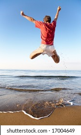 Back view of young man jumping on the beach: happiness and energy concept