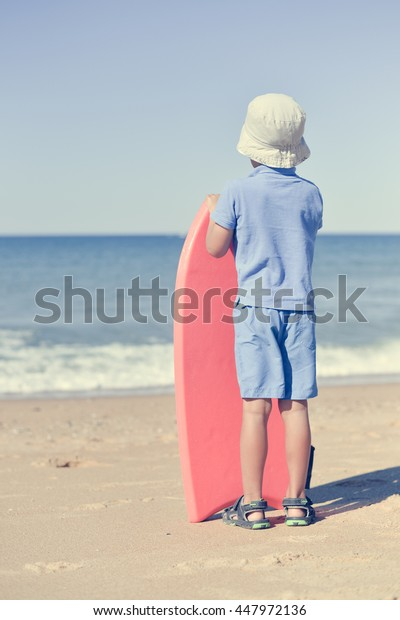 Back view of young man looking at the ocean on sunny beach, holding bodyboard