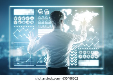 Back view of young man managing abstract digital business chart on city background. Toned image. Technology concept