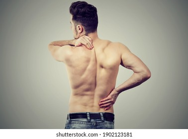 Back view of a young man with neck and lower back pain