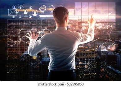 Back view of young man on rooftop managing abstract business charts and diagrams. City background. Fund management concept