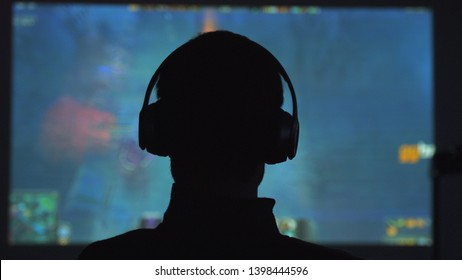 Back view of a young man plays video games in dark room watches a movie in headphones.