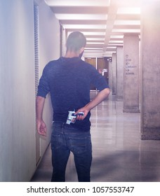 Back view of a young man pulling out a concealed silver sig safer handgun in school hallway concept