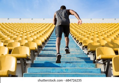 Back view of a young man running upstairs at a stadium