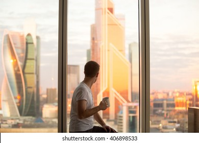 Back view of young man sitting on window with coffee cup, looking at dawn city scenery after early wakeup. Handsome casual guy relaxing in penthouse after good night sleep and watching sunrise