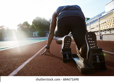 Back view of a young man in starting position for running on sports track