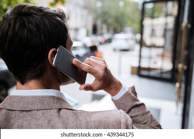 Back view of young man talking on cell phone on the street of city