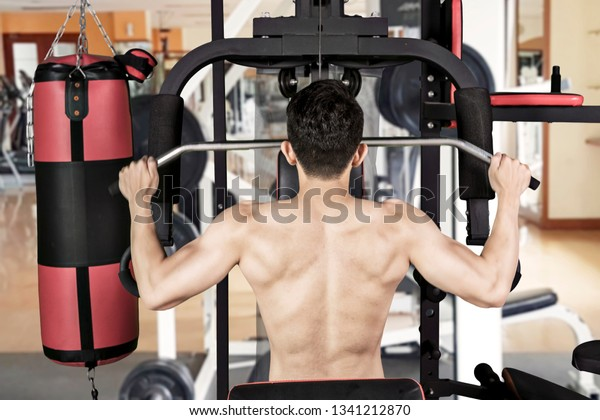 Back view of young man using fitness machine for trains his muscular arms at the gym