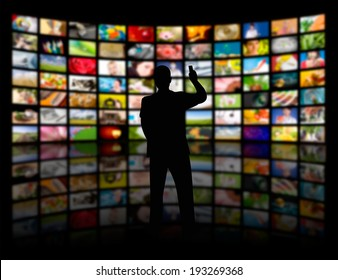 Back view of a young man watching a big TV panel