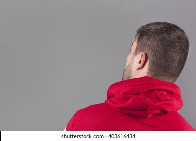 Back view of a young man wearing a red sweatshirt on grey background
