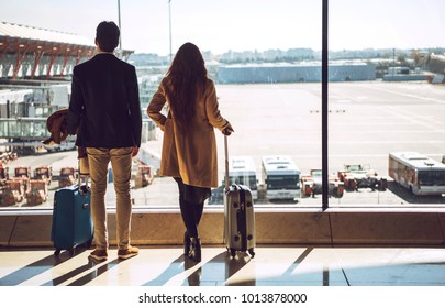 Back view of young man and woman standing with baggage at window in terminal of airport.