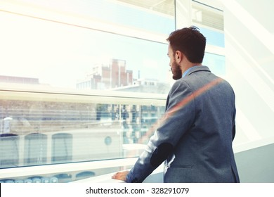 Back view of a young men entrepreneur thinking about something while looking in big office window, successful serious businessman dressed in elegant luxury clothes enjoying calm after hard work day