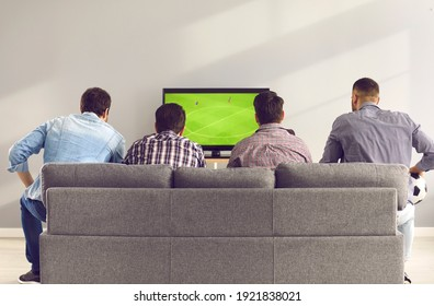 Back view of young men sitting on comfortable grey sofa and watching live football game on TV. Group of 4 friends relaxing on soft couch at home and enjoying interesting soccer match on television