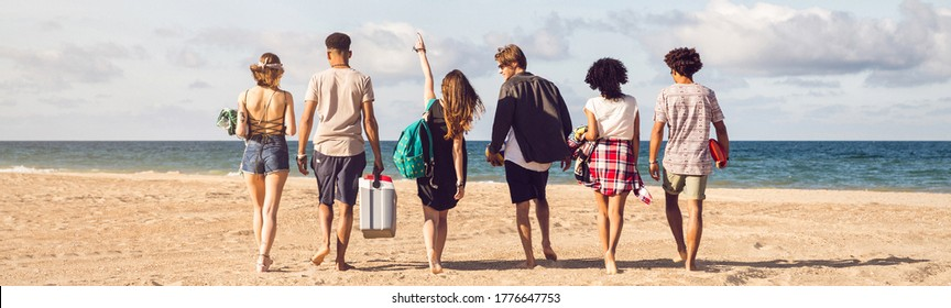 Back view of young men and woman walking on sea shore