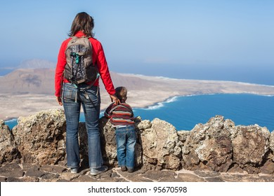 Back view young mother with backpack and son standing on cliff's edge and looking to a island.