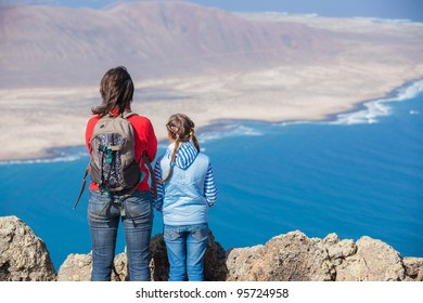 Back view young mother with backpack and daughter standing on cliff's edge and looking to a island.