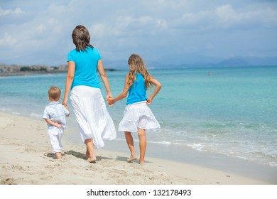 Back view of young mother with her two kids on tropical beach vacation
