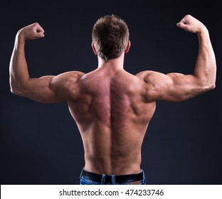 back view of young muscular man showing his muscles over black background
