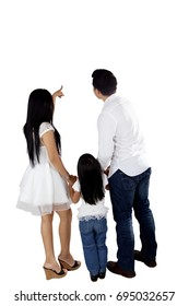 Back view of young parents pointing and looking at something while holding their hands daughter, isolated on white background