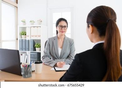 back view of young pretty girl joining company interview looking for job and talking with smiling elegant office manager woman.