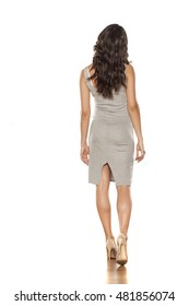 back view of a young pretty woman walking in a short dress and high heels